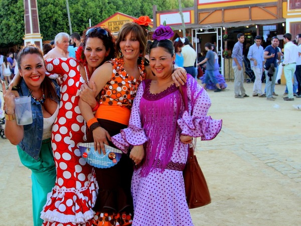 Four women at the annual Feria de Caballo in Jerez de la Frontera pose for a photo on their way to enjoying a pitcher of rebujitos made with fino sherry.