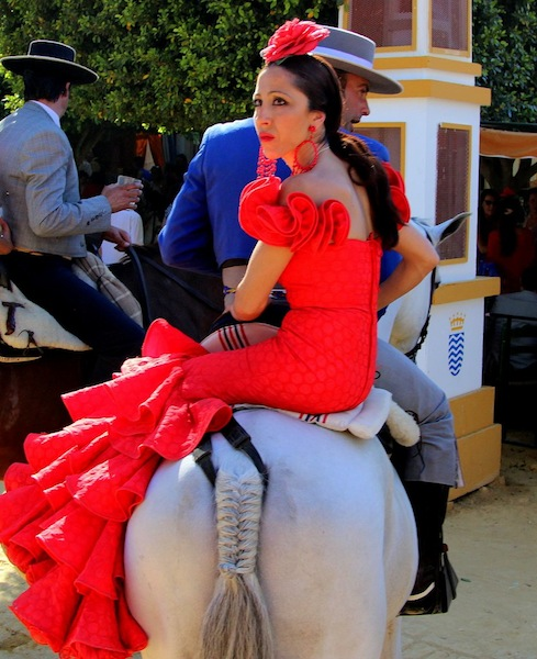 A couple rides in the Feria de Caballo.