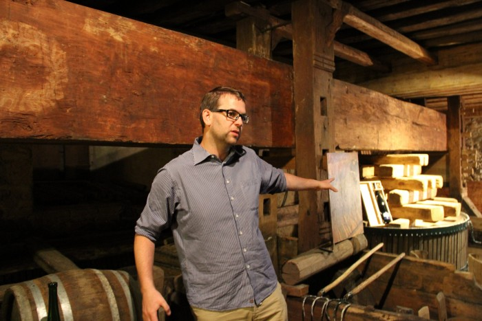 Nikolaus Saahs stands in front of a 350-year-old beam press